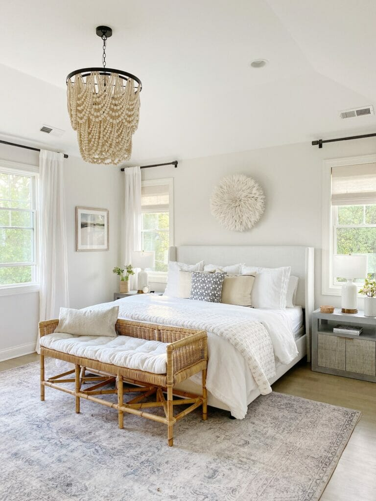 Neutral bedroom design features Loloi loren rug in slate, Wayfair upholstered bed in zuma white, rattan bench, beaded chandelier, and Benjamin Moore classic gray walls at 50% strength.