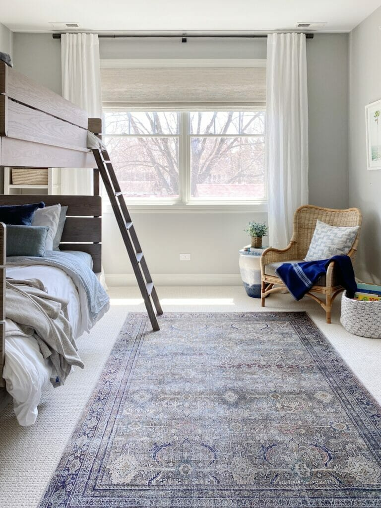 Boys bunk room features pretty Loloi Layla rug in olive charcoal, rattan chair from Wayfair, woven wood roman shades and white linen curtains, and Benjamin Moore harbor gray walls.