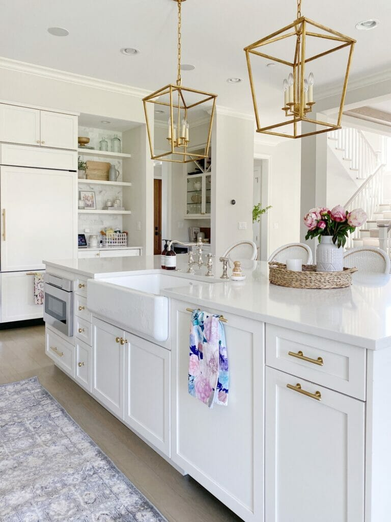 Walmart spring decor trends, sharing my favorite home decor and outdoor furniture accessories to prep for warmer months ahead! White kitchen features Walmart runner, brass hardware and Darlana lanterns, Benjamin Moore classic gray walls, open shelving with marble subway backsplash.