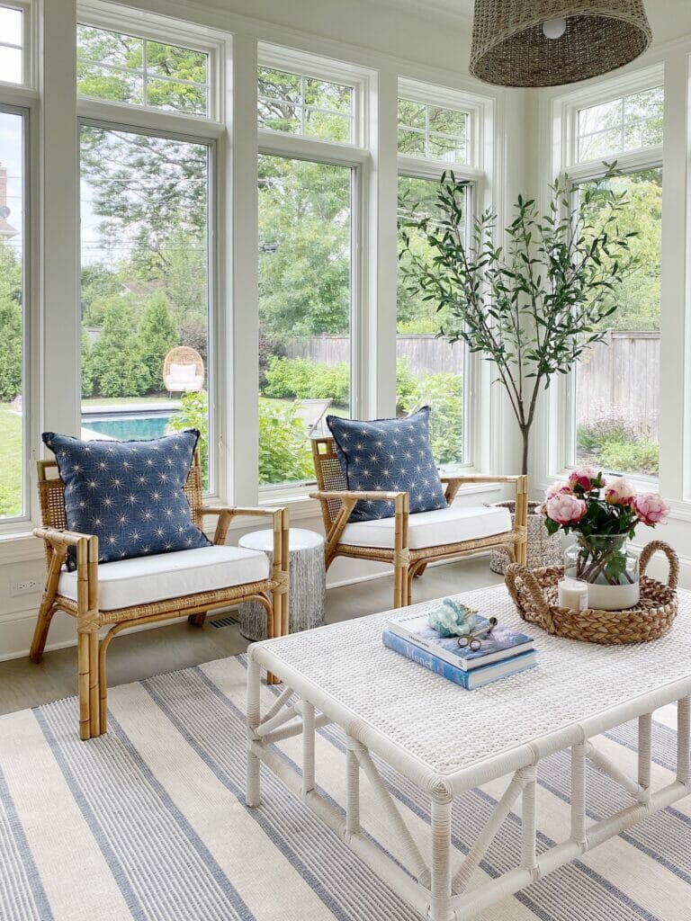 Sunroom space features wall of windows, pretty rattan chairs, woven indoor outdoor coffee table, Wayfair striped rug, and faux olive tree.