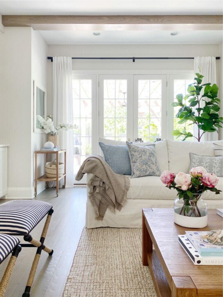 Light filled spring living room with white slipcovered sofas, wool jute rug, striped stools from Wayfair, linen curtains, and pretty faux fiddle.