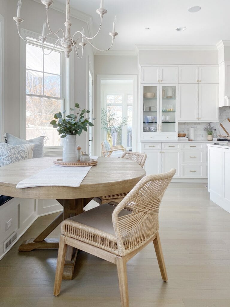 White kitchen features glass cabinets, banquette table with pretty woven chairs from Wayfair, antique inspired chandelier, and Benjamin Moore classic gray walls.