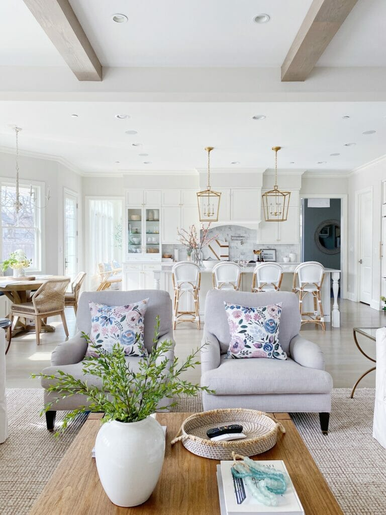 Open kitchen and living room design, Serena and Lily riviera stools and Darlana brass lanterns. White kitchen cabinets and benjamin moore classic gray walls.