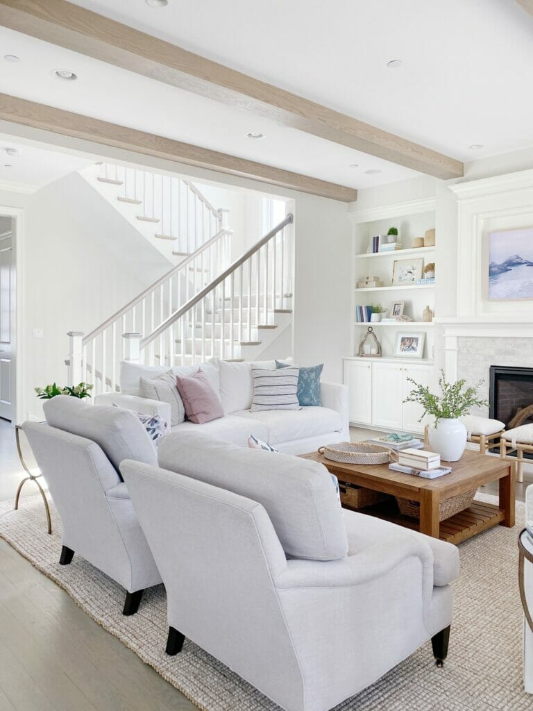 Light and bright living room features white covered slipcovered sofas, upholstered chairs, Pottery Barn wool jute rug in natural, Benjamin Moore classic gray walls, wood square coffee table, pretty bookshelf styling and summery pillows.