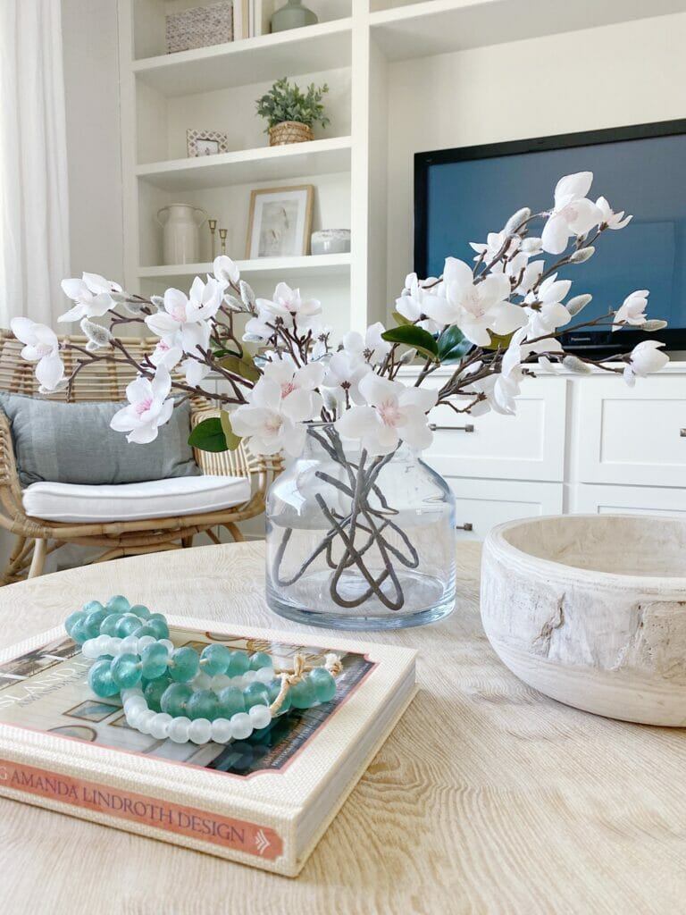 Coffee table styling, glass vase with affordable faux stems, wooden bowl, and pretty sea hued bead make the perfect styling combo.