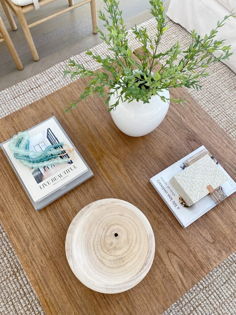 Square coffee table styling, coffee table books add visual interest and create height when layered with beads or boxes. Pretty vases and bowls also create visual interest.