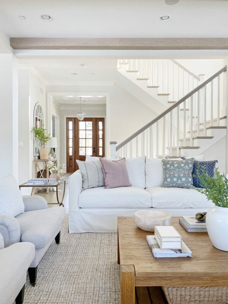 Living room and open staircase, features white slipcovered sofa and upholstered chairs. Wood coffee table and Pottery Barn wool jute rug in natural. Benjamin Moore classic gray walls.