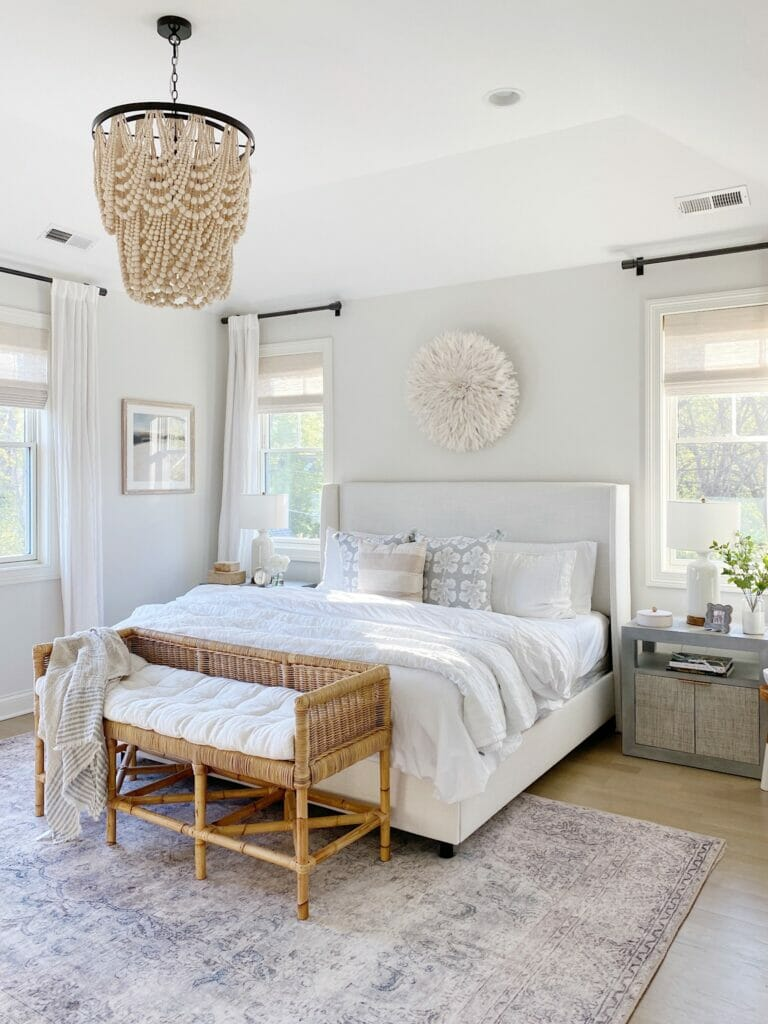 Bedroom features pretty neutral styling, Loloi Loren rug in slate, upholstered bed, rattan bench, benjamin moore classic gray walls.