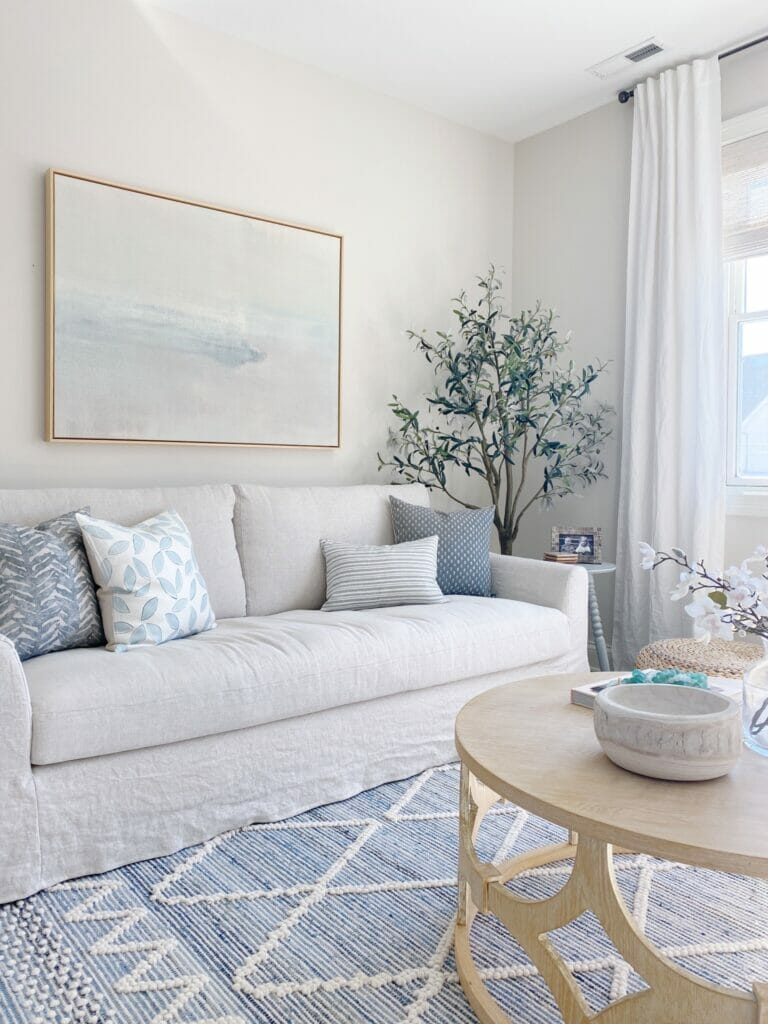 Living room features Serena & Lily Ryder denim rug, Benjamin Moore classic gray walls, pretty abstract art and Ikea farlov sofa, swivel chairs and simple coffee table styling.