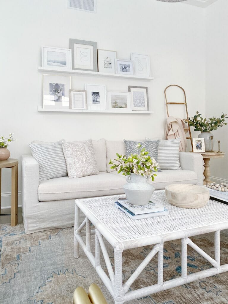 Living room features Pottery Barn Finn rug, Benjamin Moore simply white walls, slipcovered sofa and woven coffee table.