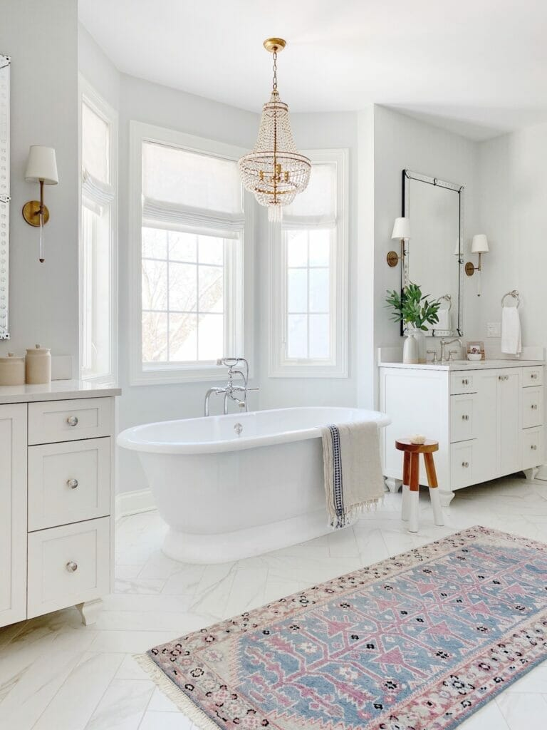 Bathroom features Caitlin Wilson vintage inspired runner, Serena & Lily dip dyed stool in tall, double vanities, pretty brass sconces and quartz countertops. Paint color is Benjamin Moore paper white.