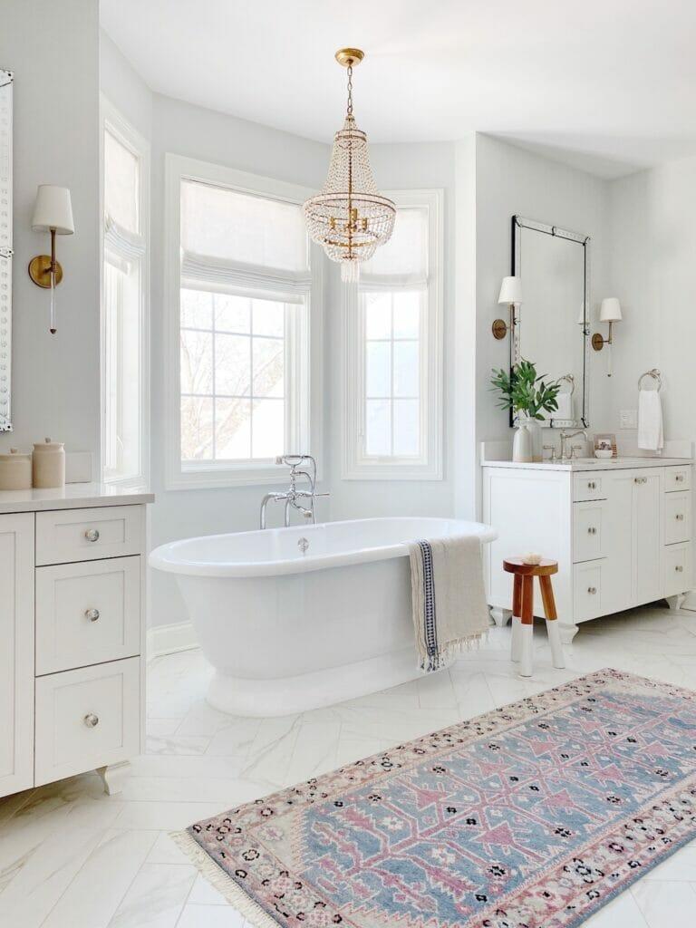 Bathroom features this beautiful Caitlin Wilson runner, herringbone tile, a freestanding tub and double vanities.