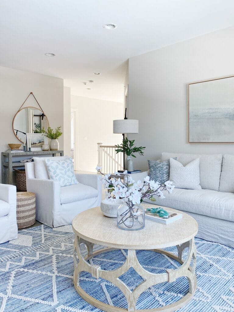 Living room features Serena & Lily ryder denim rug, Ikea farlov sofa, and swivel upholstered chairs.