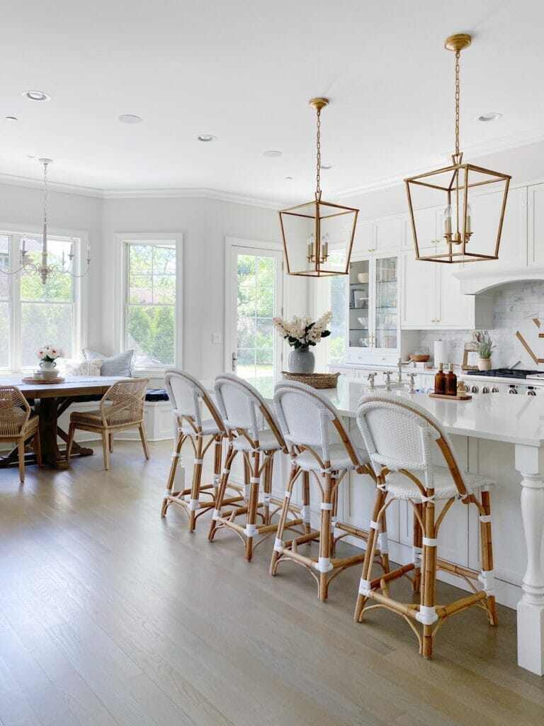 White kitchen features Serena & Lily Riviera stools in white, brass Darlana lanterns, quartz counters, white kitchen cabinets with a marble subway tile backsplash.