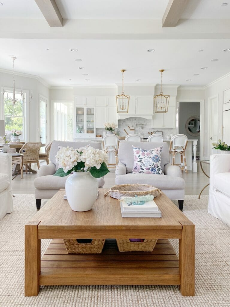 Summer living room with square wood coffee table, light grey upholstered chairs, open to kitchen with brass lanterns and white Serena & Lily riviera stools. Walls are benjamin moore classic gray.