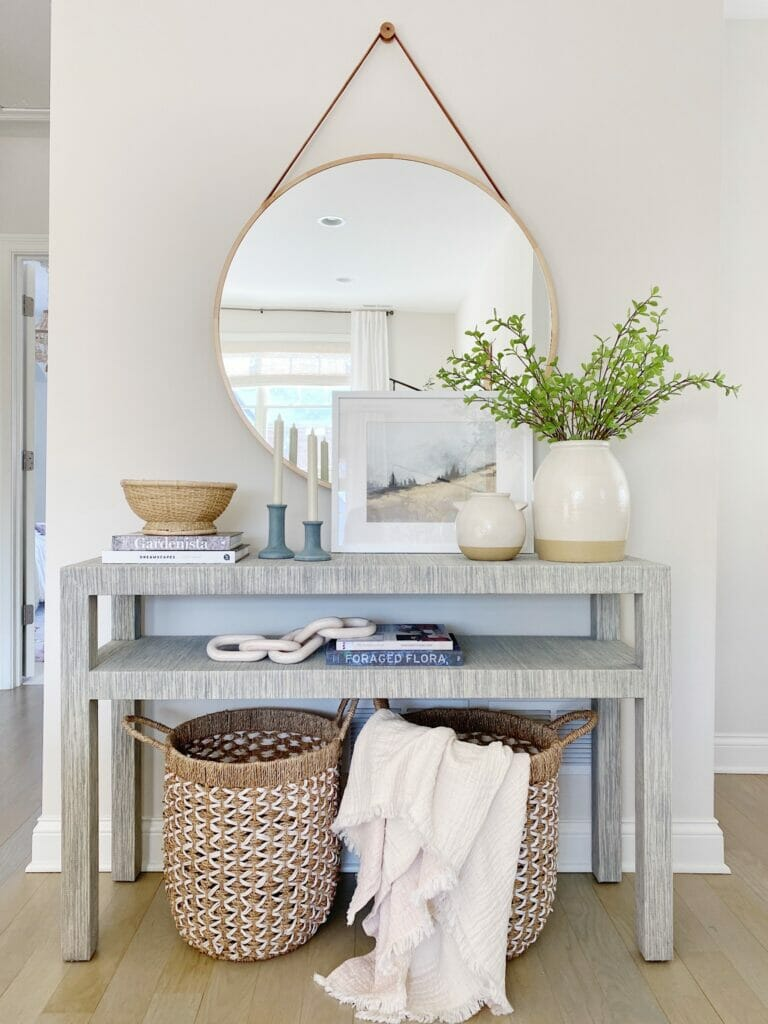 Serena & Lily Black raffia console table in fog, paired with a pretty round mirror and fresh spring styling.