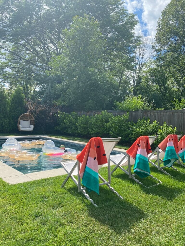 Backyard pool with concrete surround and sling chairs