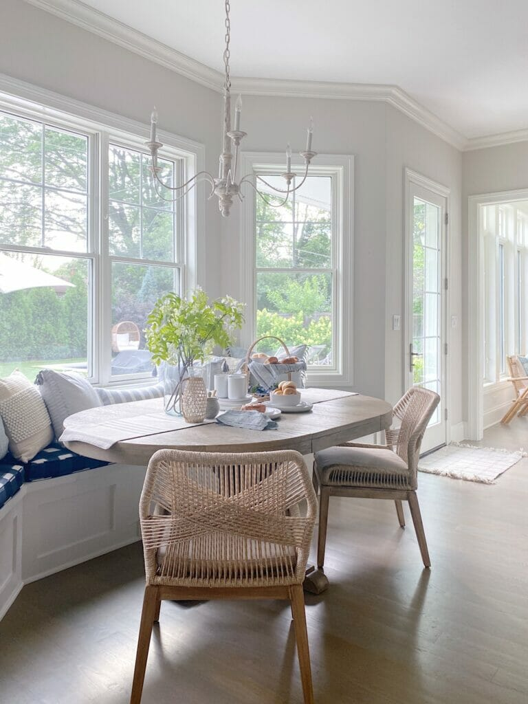 Kitchen banquette featuring Gap Home kitchen pieces and pretty affordable pillows, woven chairs, Benjamin Moore classic gray walls.
