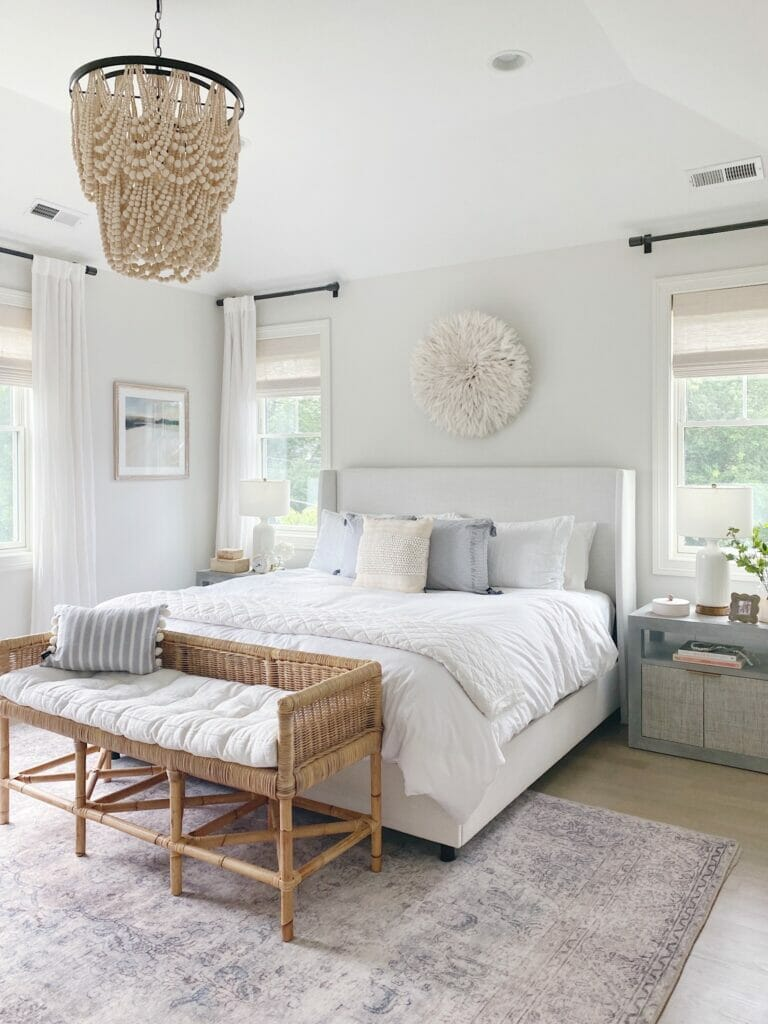 Bedroom featuring Gap Home pillows and frayed edge quilt, Benjamin Moore classic gray walls, upholstered bed and rattan bench