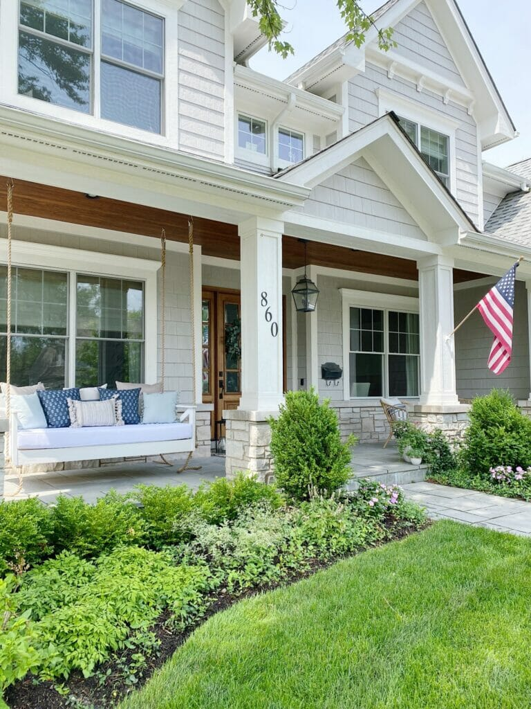 Bluestone front porch with wooden hanging porch swing, house painted in Benjamin Moore smoke embers.