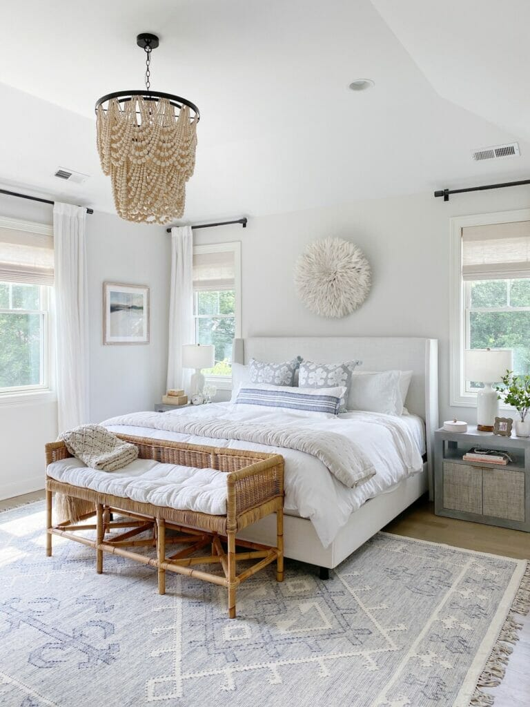 Coastal bedroom features upholstered bed, woven serena and lily bench, benjamin moore classic gray walls, beaded chandelier