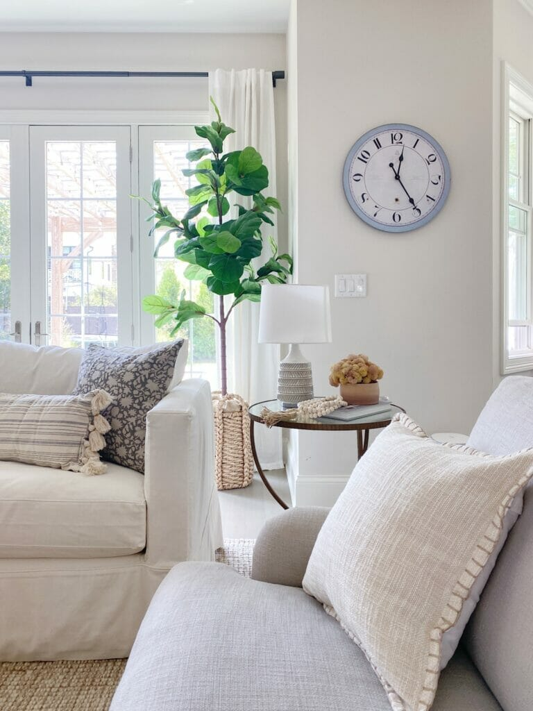 fall living room decor, pretty linen pillow, end table with textured lamp and faux fall arrangement