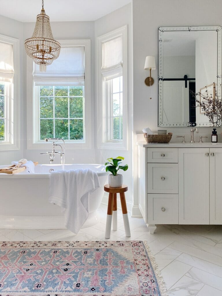 Primary bathroom features freestanding bath tub, vintage inspired rug, white vanity with large mirror and brass sconces