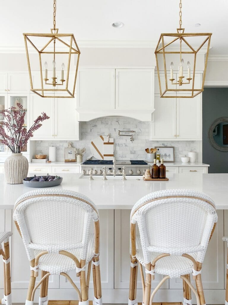 white kitchen features serena & lily riviera counter stools, brass lanterns, marble subway backsplash, quartz countertops and white kitchen cabinets