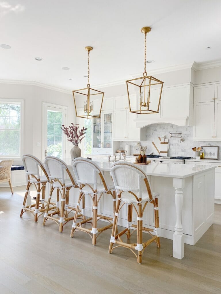 white kitchen features serena and lily riviera counter stool, brass lanterns, quartz counters and marble subway backsplash