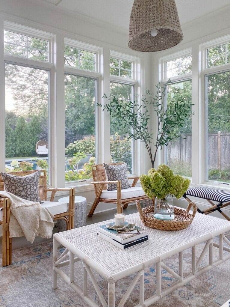 living room with large windows, coffee table, rattan chairs, faux olive tree and benjamin moore simply white paint
