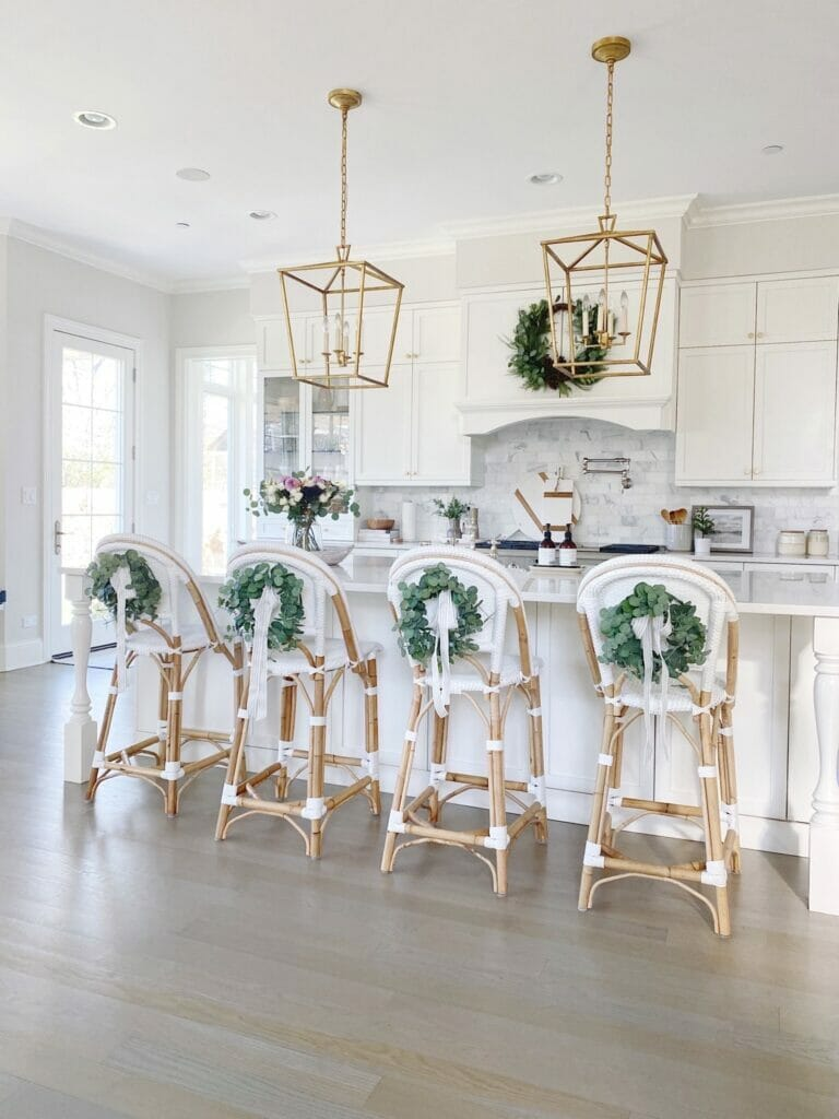 Life On Cedar Lane Holiday Shopping Guide   Christmas kitchen with eucalyptus wreaths on counter stool backs, faux wreath on kitchen hood