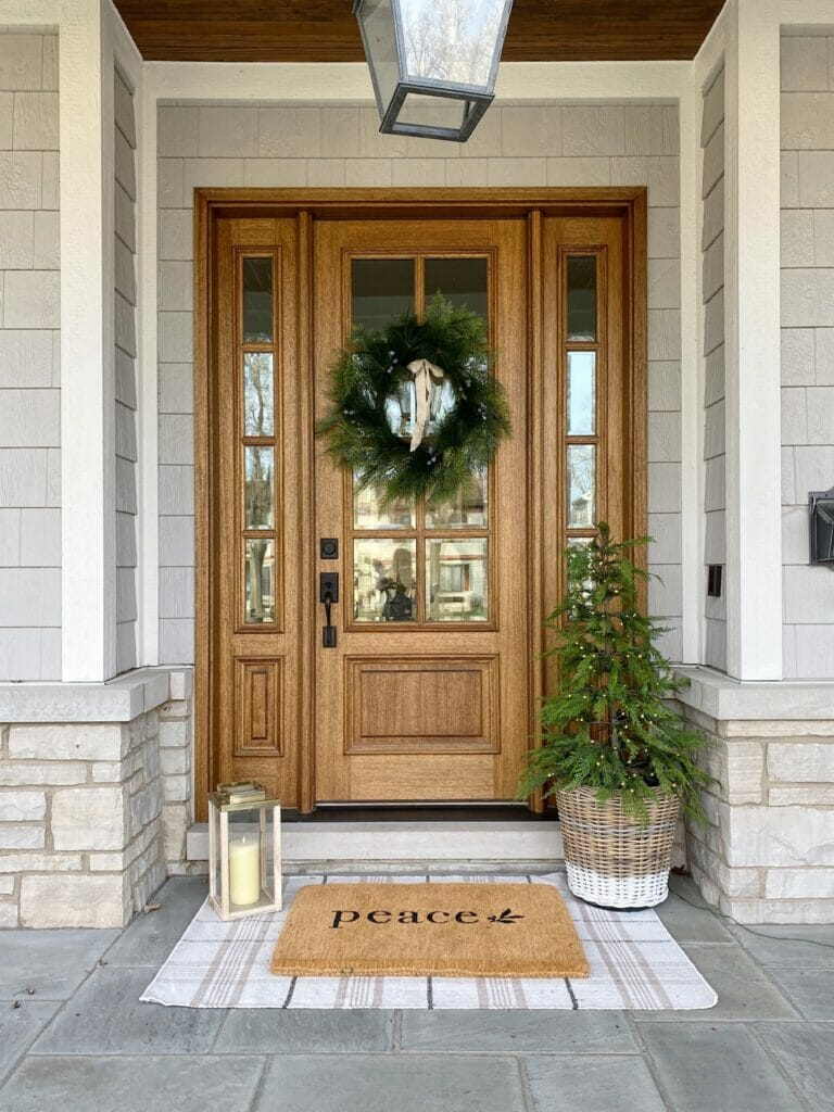 Christmas front porch features faux wreath, pre lit tree and cute christmas door mat