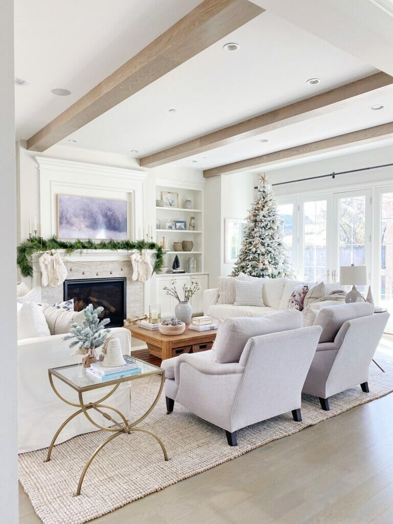 Life On Cedar Lane Holiday Shopping Guide   Neutral living room with faux christmas tree, pretty holiday mantle decor and festive coffee table styling